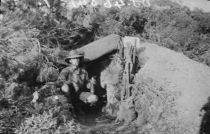 Soldier holding a Turkish shell at entrance to dug-out, Gallipoli, Turkey