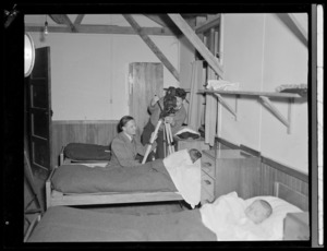 Two men filming sleeping children, in boys' dormitory at Polish children's refugee camp, Pahiatua