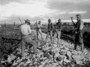 Men breaking up rocks for road construction