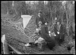 Group having a picnic in bush beside the Taieri River, with a whitebait net nearby.