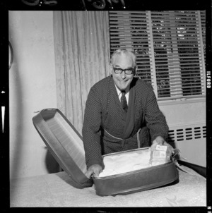 Prime Minister Keith Holyoake packing his bags for an overseas trip