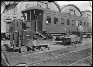 Scene outside unidentified railway workshops, with two men with laden trolleys in front of a railway carriage