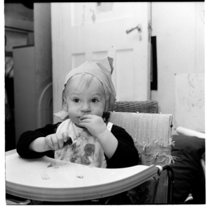 Lisa van Hulst wearing a party hat, sitting in a high chair, probably on her 1st birthday