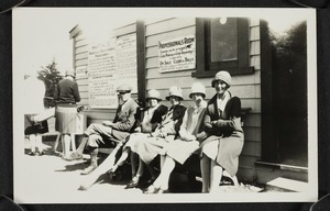 Agnes Isobel Stout and other spectators seated outside a golf pavilion