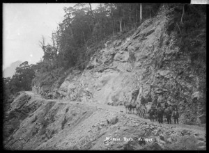 View of the Maruia Road. A group of men are travelling with a laden four-horse drawn cart up a winding hill