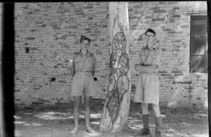 Sgt L barton and R L Kay beside Maori carving on a tree in the village of Suani Ben Adem, Libya - Photograph taken by W Timmins