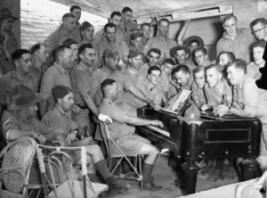 Soldiers singing around a piano at the YMCA in Maadi, Egypt, during World War II