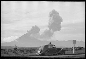 Man watching Mt Ngauruhoe eruption from Desert Road