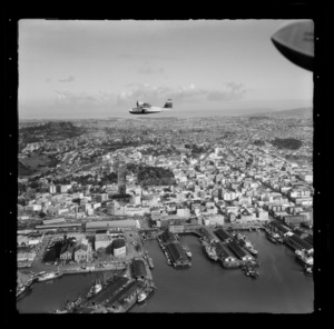 Tourist Air Travel, Grumman Widgeon aircraft in flight above Auckland Wharves