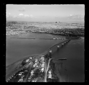 Tourist Air Travel, Grumman Widgeon aircraft in flight above Auckland Harbour Bridge