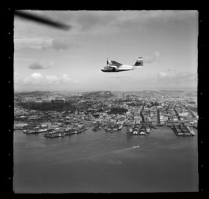 Tourist Air Travel, Grumman Widgeon aircraft in flight above Auckland Wharves and central city