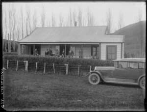 Group standing on verandah of house, with Humber in front, probably Hawkes Bay