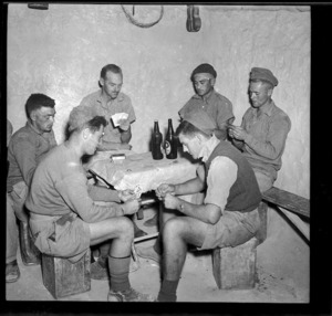 New Zealand soldiers playing cards in the corner of a dugout, during World War II
