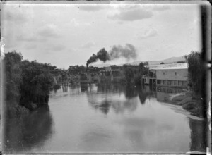 "Waihou River at Te Aroha, showing ""N"" class steam locomotive with the Auckland to Thames Express on the railway bridge."