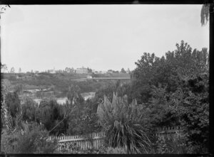 View of Hamilton, Waikato Region, from the garden at Mrs Gwynne's Cottage, including the first traffic bridge, the Waikato River, and from left, St Andrew's Presbyterian Church and Le Quesne's Hotel (3 storey building), and the adjoining Hamilton Hall