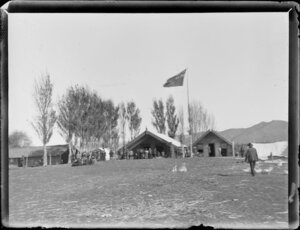 Scene during the Maori parliament (Kotahitanga) at Pakirikiri Pa, Gisborne Region, featuring the meeting house and New Zealand flag