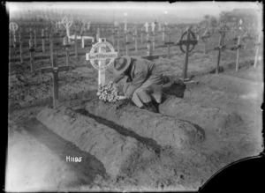 An Auckland officer placing a wreath on the grave of Lieutenant W P Richards, near Abeele, France