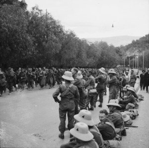 Italian prisoners of war passing New Zealanders of 24th Battalion, A Company, on the road between Piraeus and Athens