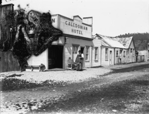 View of M McBrides' Caledonian Hotel, with older man out front, Okarito, Westland District