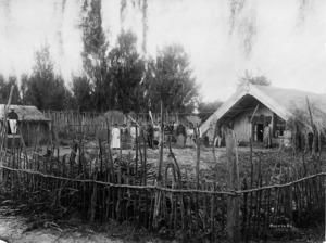 People standing next to the meeting house at Maketu Pa, Bay of Plenty