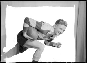 Rugby player posing with ball in studio