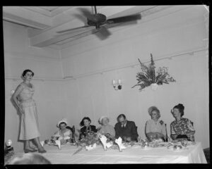 Model parading on table, people seated, eating