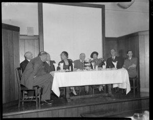 People seated at table on stage