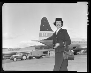 Air hostess [Miss Clark] in front of Teal plane