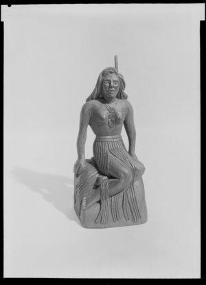 Maori souvenir - wahine seated on rock