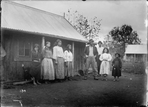 Maori family group in front of a wooden building