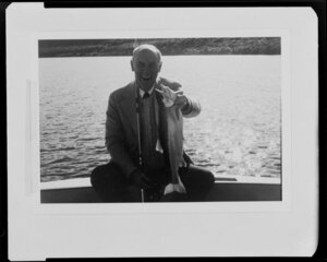 Man holding trout by lake