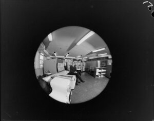 Fish-eye portrait of man with computers
