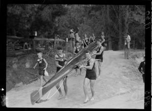 New Zealand men's eights rowing team carrying boat to water, 1950 British Empire Games, Lake Karapiro