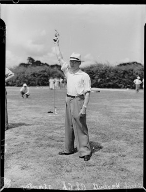 Starter Cliff Harbutt with his pistol in the air, 1950 British Empire Games