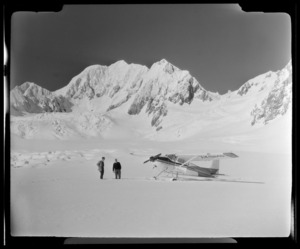 Two men standing next to a Mount Cook Air Services aeroplane at Fox Glacier