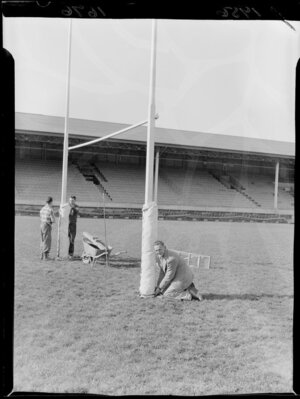 Mr Meates, groundskeeper at Athletic Park, Wellington, tying protective pads on the goalposts with the help of two unidentified men