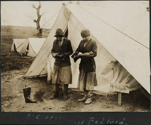 Doctor Cooper and Miss Bedford cleaning boots outside a tent, Serbia.