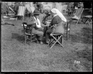 A wounded World War I soldier talking to a nurse at the garden party in the grounds of the New Zealand Stationary Hospital