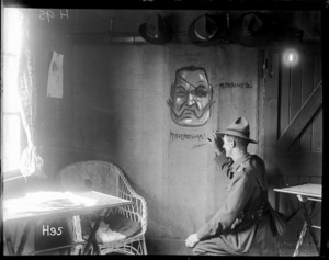 The New Zealand unofficial cartoonist, Lt G. Pat Hanna, beside his cartoon on the wall of the officers' club during World War I