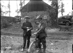A New Zealand soldier delivers a message to a French villager, Grevillers