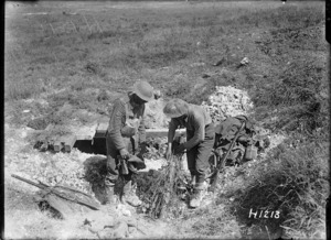 New Zealand soldiers camouflaging a gun during World War I, France