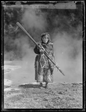 Marutuna of Orakeikorako dressed in a feather cloak holding a taiaha