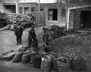 Relief workers shovelling coal into sacks, probably in Wellington