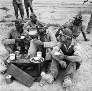 Members of the New Zealand Railway Construction Company having a snack, Western Desert