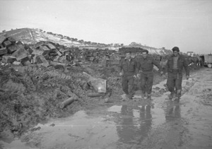 Three members of the New Zealand forces tramping through mud and snow at the front in Italy during World War II