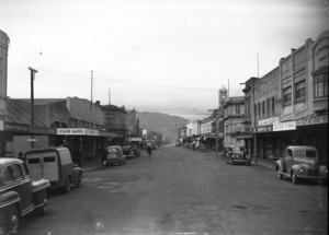Looking down Jackson Street, Petone, close to Scholes Lane, with R W Short & Co and, a van advertising Madeline Cake Kitchen, on the left and the Quality Cake Kitchen, Davidson's chemist and Macduffs Ltd on the right