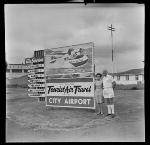 Fred and Mabel Ladd with Tourist Air Travel sign, Auckland Airport