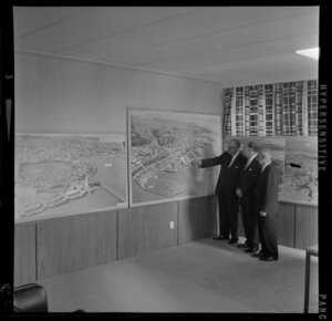 Unidentified men looking at exhibition of Whites Aviation photographs, Auckland Harbour Board