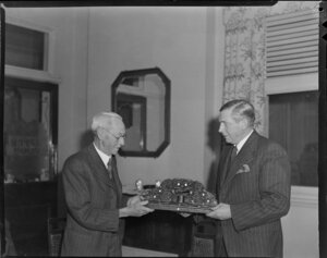Sir Leonard Monk Isitt presenting a Maori wood carving to Tasman Empire Airways Ltd's retiring chairman Mr Rudder