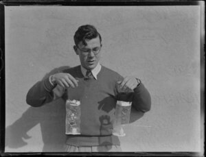 Unidentified man with [candle lanterns ?], Tasman Empire Airways Ltd, [med section ?] Auckland